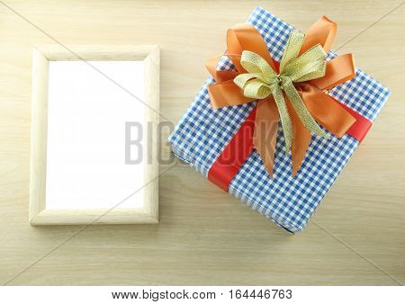 Blue gift box place near wooden frame on the wood floor in concept of Christmas and Valentine day or New year.