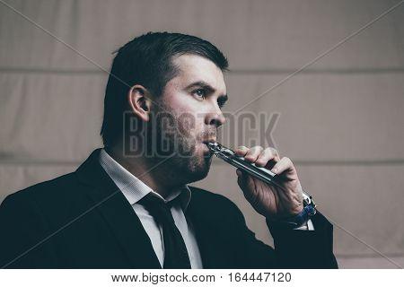 Young businessman smoking electronic cigarette. Close-up portrait