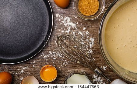 Ingredients for pancakes, frying pan, whisk on brown background