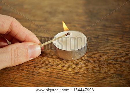 Male hand holding an ignited safety match stick before igniting white candle on the wooden surface