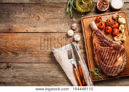 Succulent grilled tomahawk beef steak on the bone with seasonings, fresh rosemary and grilled vegetables on wooden background, top view