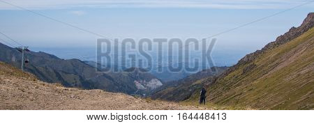 Young couple are standing at Talgar pass and looking on the city Tien Shan mountains near Shymbulak ski resort Almaty Kazakhstan 2016