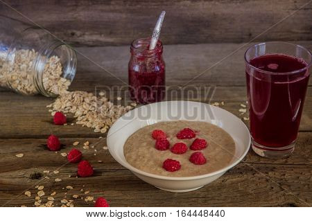 Oatmeal Porridge With Raspberries And Compote On The Wooden Table