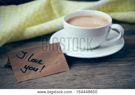 Note I love you with cup of coffee on wooden table