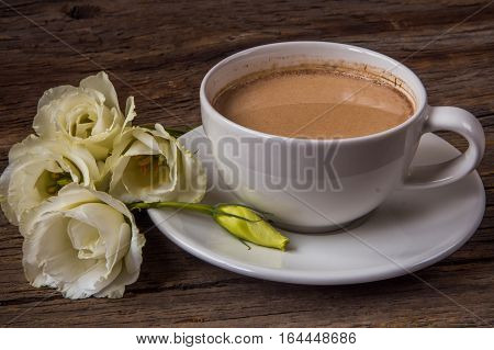 Still life with cup of coffee and flowers Eustoma on wooden table