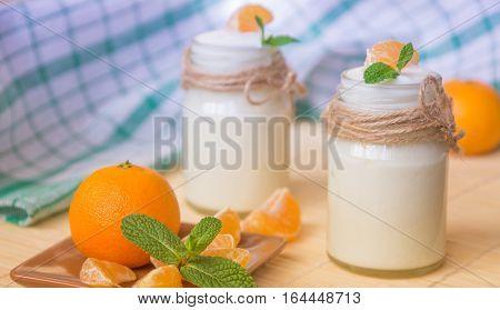 Fresh organig natural white yogurt in glass jars with tangerine and green mint