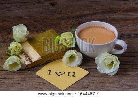 Coffee cup with spring flower lisianthus and notes I love you on wooden table