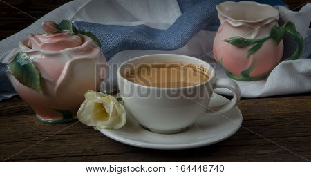 Cup of coffee with milk red grapes pink crockery and eustomas on wooden table