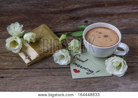 Coffee cup with spring flower lisianthus and notes good morning on wooden table