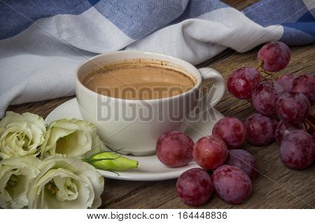Still life with cup of coffee and flowers Eustoma and red grapes on wooden table