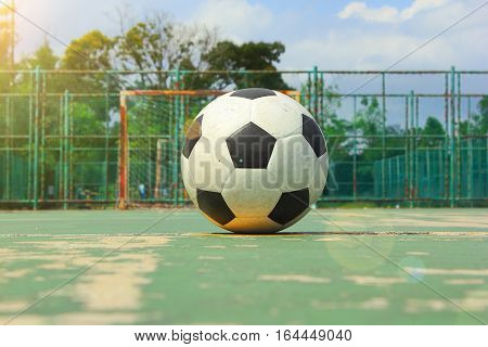 The ball on the middle of futball court and futsal goal as the background with sun flare