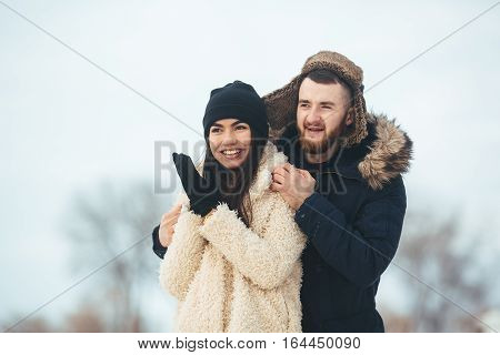 man and woman posing for the camera in the park