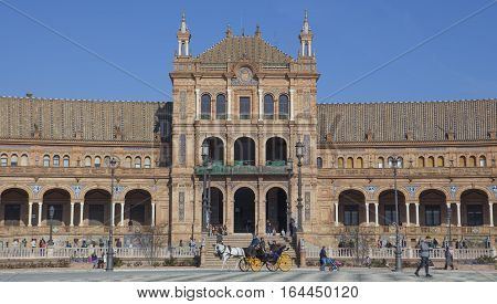 Seville Spain - January 2 2017: Horse drawn carriage crossing the Plaza de Espana Seville Spain. Backlight