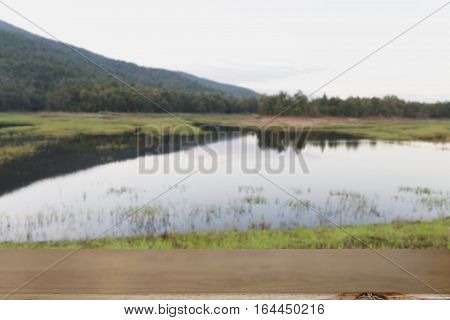 Blur Background Of Mountain And Pond In Park With Selected Focus Empty Wood Table For Display Your P