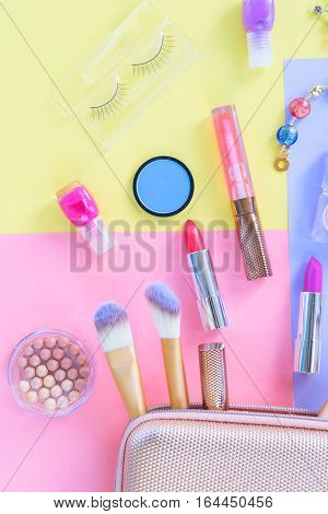 Colorful make up products with pursue pop art flat lay scene