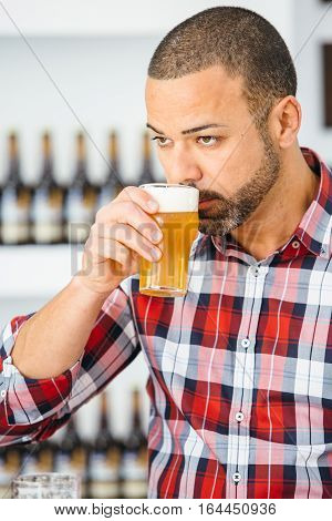 Portrait of bearded man in checked shirt smelling light craft beer