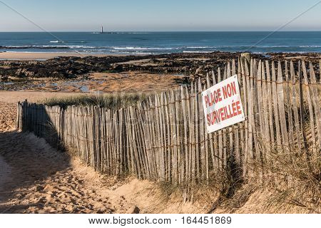 French sign Unguarded beach on wood fence, beach of la Paracou in la Chaume district of Les Sables d'Olonne (France)