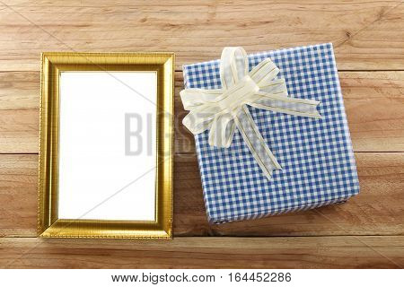 Blue gift box place near gold wooden frame on the wood floor in concept of Christmas and New year.