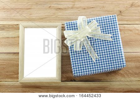 Blue gift box place near wooden frame on the wood floor in concept of Christmas and New year.