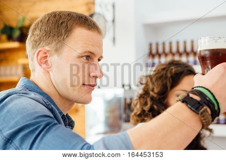 Side view of handsome man with dark craft beer in glass