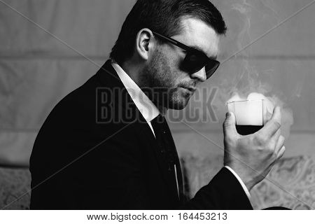Stylish young man in sunglasses looking at steaming drink a glass in his hand