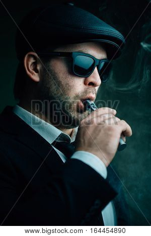 Fashionable man in sunglasses and a leather cap smokes an electronic cigarette