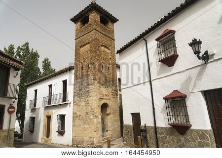 Ronda (Andalucia Spain): old typical street with white houses and a tower