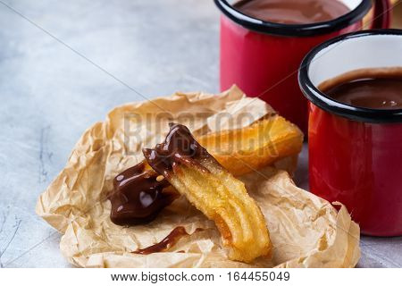 Fast junk unhealthy fat food concept. Spanish churros with hot chocolate in a mug on a rustic table. Treat for traditional typical breakfast