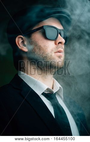 Fashionable male wearing sunglasses and a leather cap in the smoke