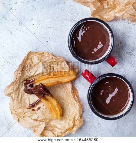 Fast junk unhealthy fat food concept. Spanish churros with hot chocolate in a mug on a rustic table. Treat for traditional typical breakfast, top view overhead flat lay