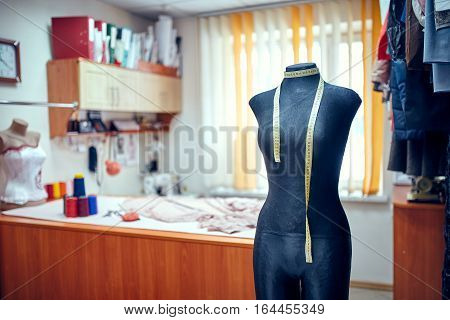 Tailor dummy with measuring tapes in fashion studio