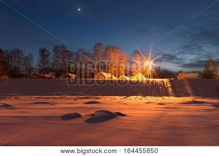 Winter evening in the Russian village. Veliky Ustyug Russia. View from the frozen river Sukhona. Travel to the North of Russia.