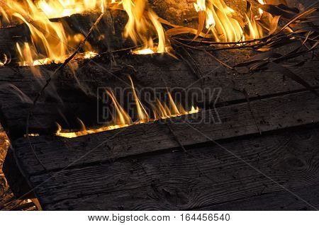View of wooden board engulfed in flames