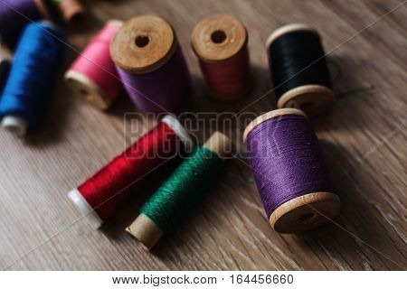 colored spools of threads in wooden background