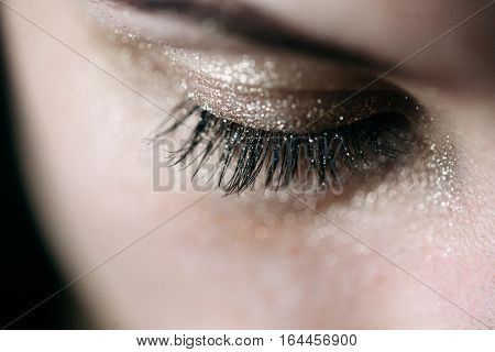 Close-up of closed eye with bright fashion golden eyeshadow