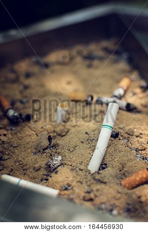 Cigarette butts discarded in ashtray ,vintage tone