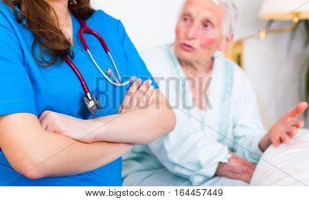 Condident doctor standing next to elderly woman's bed who is talking to her.