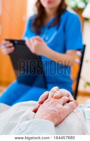 Senior patient's hands folded in bed in residential care home and a nurse in the background examining the patient.