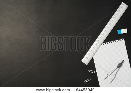 Black chalkboard office table or desk seen from above. Top view product photograph. Shool or university concept image with set of accessories