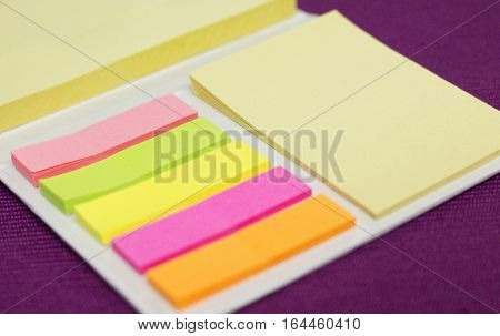 Colorful adhesive postits on the purple table in the office.