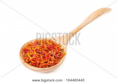 Safflower petals in wooden spoon on white background.