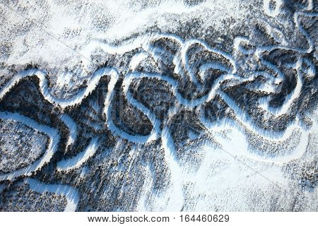 Aerial view of forest river which is on woodland in the sunny winter day during a flight.