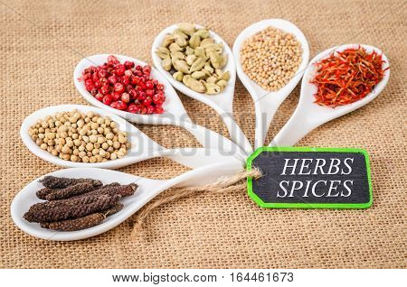 various spices and herbs with herbs spices label on sack background.