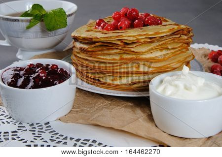 Pancakes Served With Sour Cream, Fresh Cranberries And Cranberry Jam.