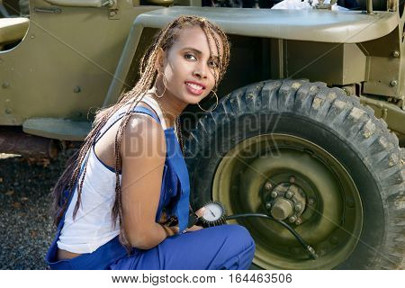 young African American woman mechanic inflates a tire