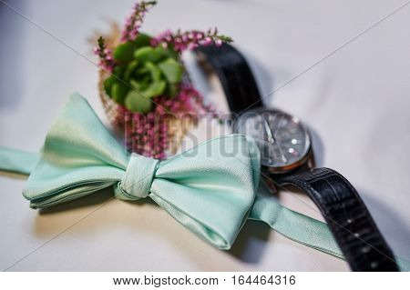man watches and turquoise Butterfly on table.