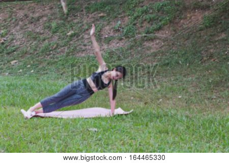 young girl practicing yoga exercises on mat outdoor in park. calmness and relax concept woman happiness (blur image)