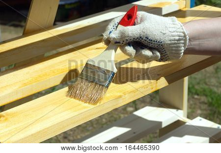 Female hand in textile glove paints a wooden shelving outdoors closeup