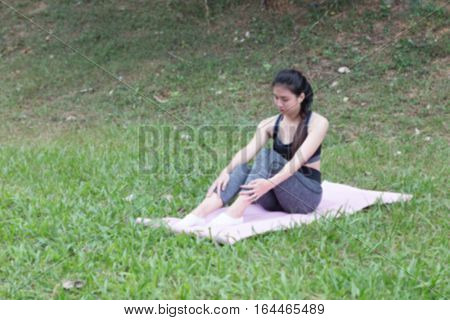 Young Woman Sitting On Mat After Exercises Outdoor In Park,  Relax In Nature (blur Image)