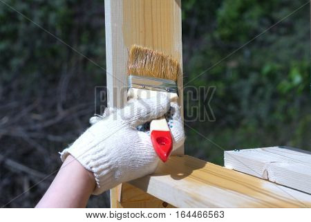 Female hand in textile glove paints wooden shelving outdoors closeup
